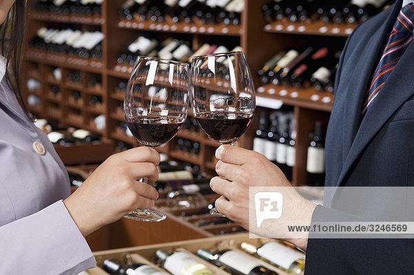 Paar stößt an mit Wein in einer Bar Gläser