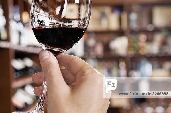 Man's Hand hält ein Glas Wein in einer bar Man's Hand hält ein Glas Wein in einer bar