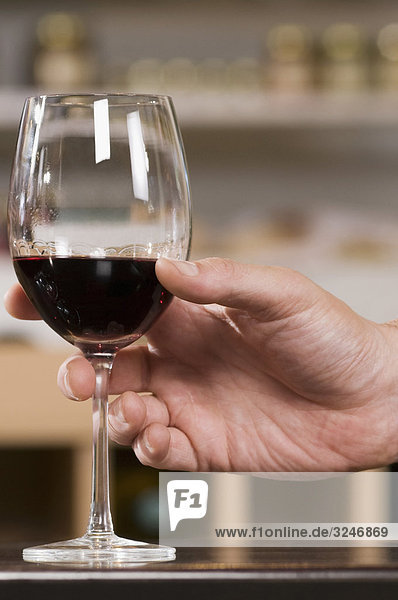 Man's hand holding a glass of wine in a bar