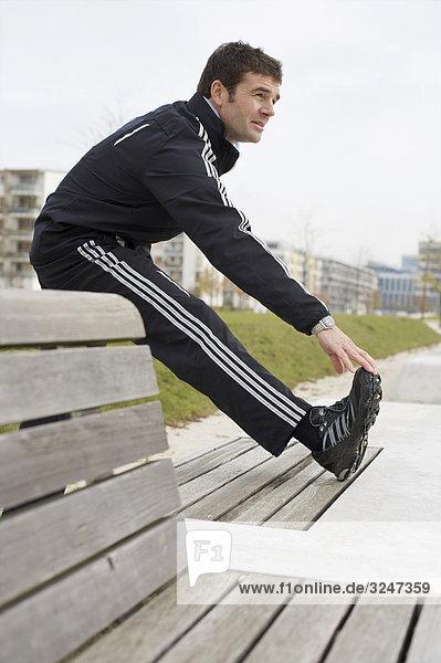 Jogger Aufwärmübungen machend  Seitenansicht
