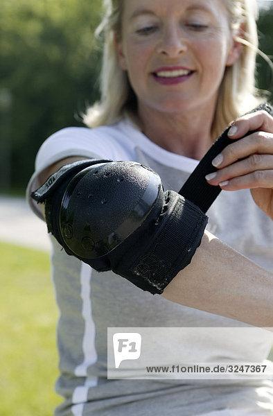 Seniorin Ellbogenschutz anziehend  Frontalansicht  Close-up