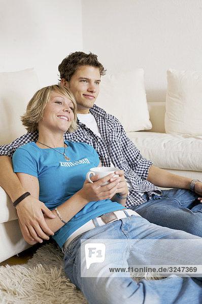 Teenagerpaar vor Couch sitzend und fernsehend  Hochformat