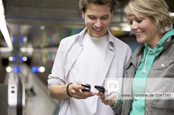 Teenager Handynummern in Bahnhof austauschend  Oberkörperaufnahme