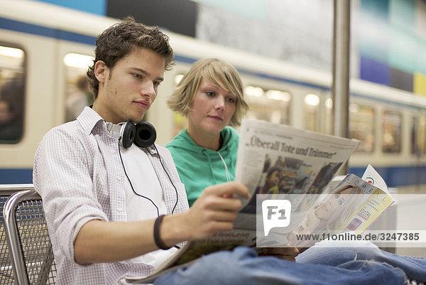 Teenagerpaar Zeitung an U-Bahnstation lesend  Querformat