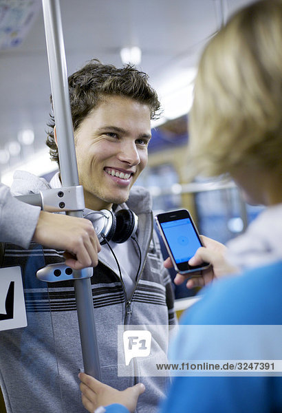 Junge flirtet mit junger Frau in U-Bahn  Schrägansicht