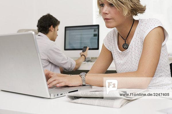 Zwei Teenager Laptop  Handy und Desktopcomputer benutzend  Querformat