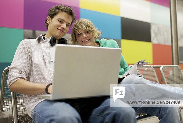 Teenagerpaar Laptop an U-Bahnstation benutzend  Flachwinkelansicht
