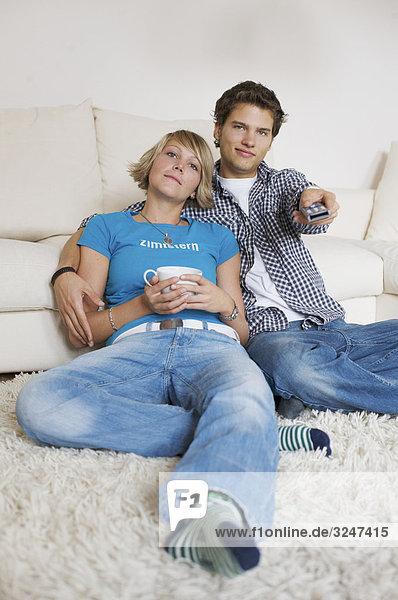 Teenagerpaar vor Couch sitzend und fernsehend  Flachwinkelansicht