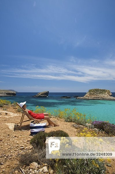 Frau sitzt im Liegestuhl  Blaue Lagune  Comino  Malta