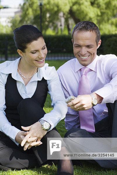 Ein Geschäftsmann und ein Geschäftsfrau sitzt auf dem Rasen  Stockholm  Schweden.
