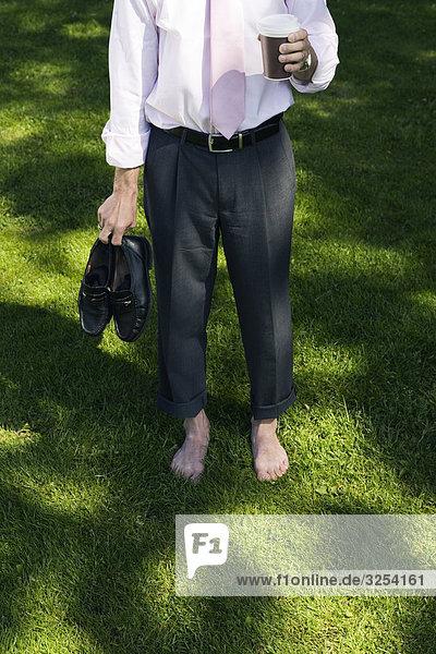 A barfuß Geschäftsmann auf das Gras  Stockholm  Schweden.