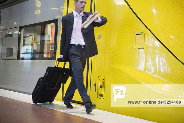 Geschäftsmann zu Fuß auf einer Plattform neben einem Zug  Stockholm  Schweden.
