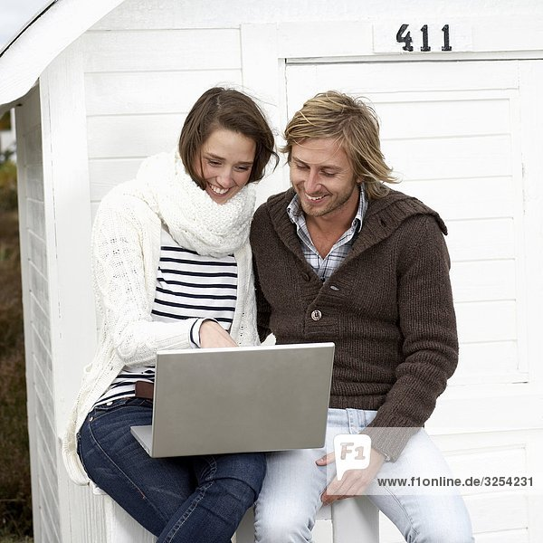 Junges paar mit einem Laptop im Freien  Skane  Schweden.