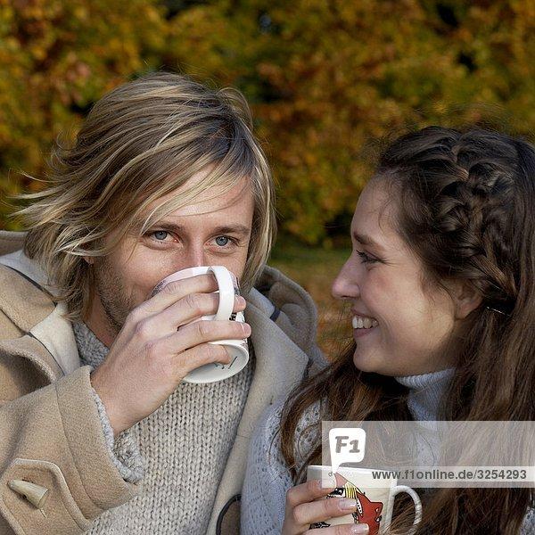 Ein paar mit eine Tasse Kaffee in einem Park  Skane  Schweden.