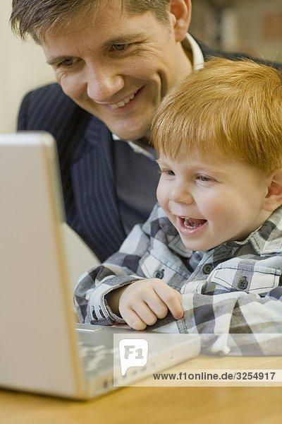Vater und Sohn mit einem Laptop  Schweden.