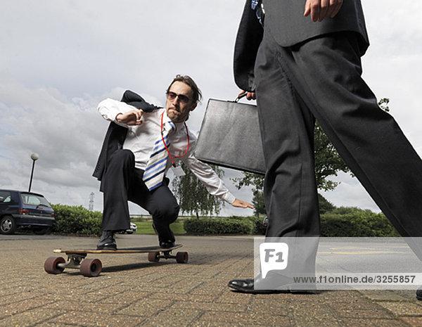 Geschäftsmann auf dem Skateboard
