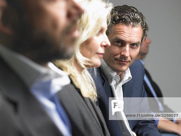 Mann schaut auf die Kamera während der Konferenz