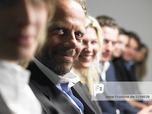 Menschen  die auf einer Konferenz in die Kamera schauen