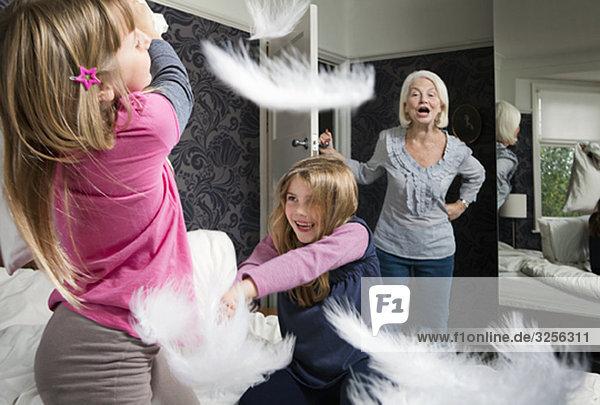 Eine Oma schreit die Kissenschlacht der Mädchen an.