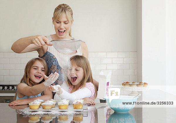 Zwei Mädchen und eine Mutter beim Backen