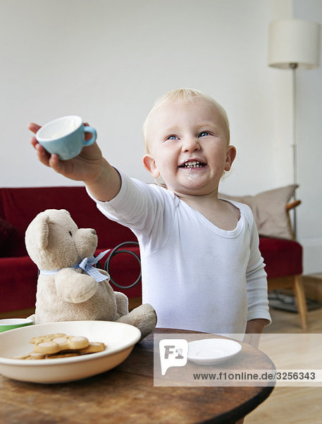 A boy toddler holding out a tea cup