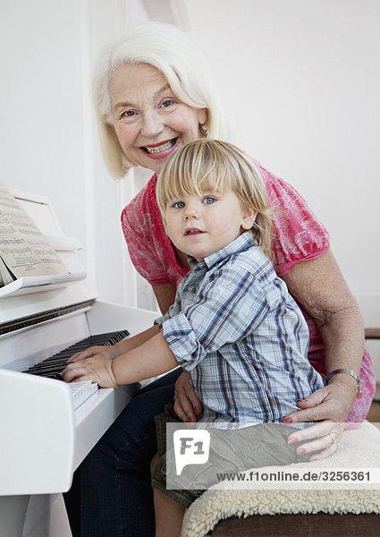 Oma und Enkel sitzen am Klavier Oma und Enkel sitzen am Klavier