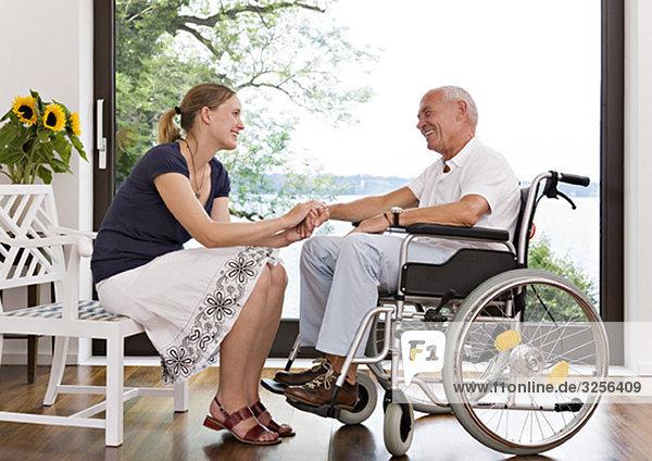 Frau mit der Hand eines älteren Mannes