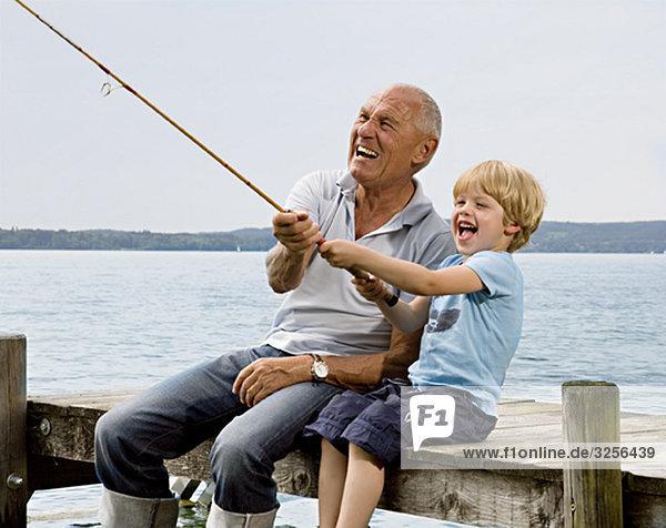 Junge fischen mit Großvater am See