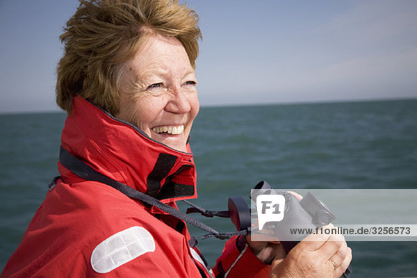 Frau mit Fernglas am Meer