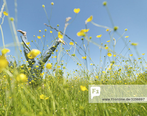 Senior woman cartwheeling through field