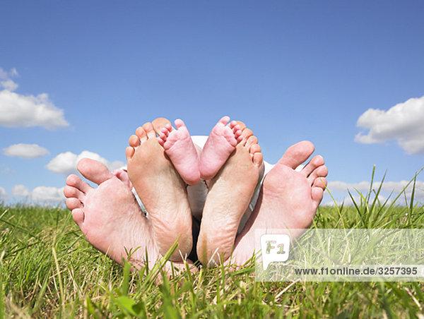 Füße der Familie im Feld liegend