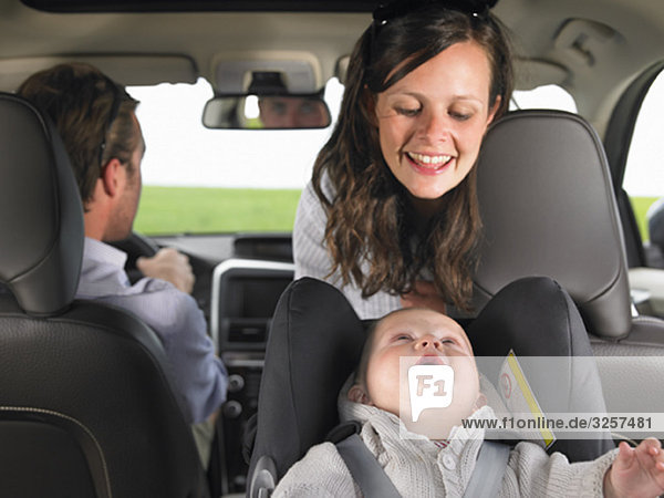 Mutter beobachtet Baby im Autositz