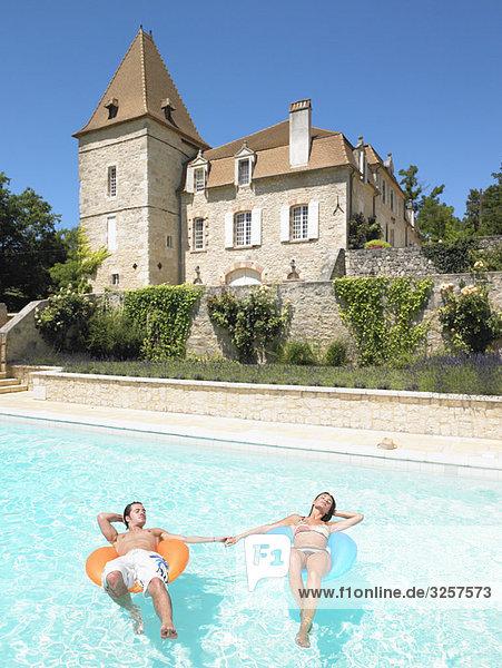 junger Mann und Frau im Pool schwimmend