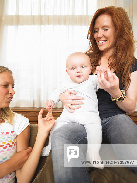 young women playing with baby
