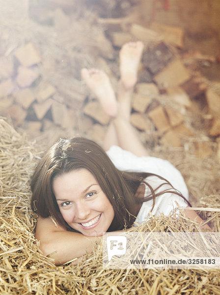 Woman lying in hay