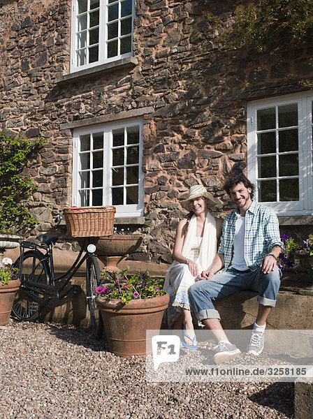 Man and woman sit outside country house