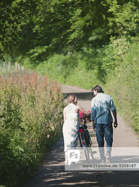 Man and woman walking up country lane