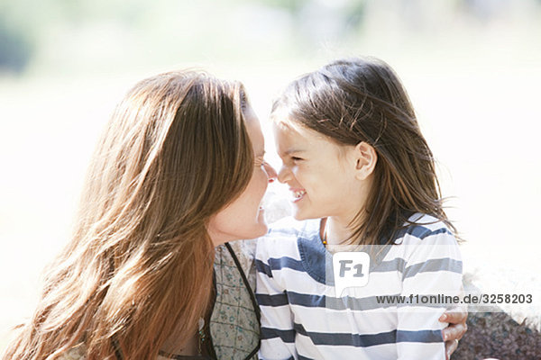 Mother and daughter smiling touch noses