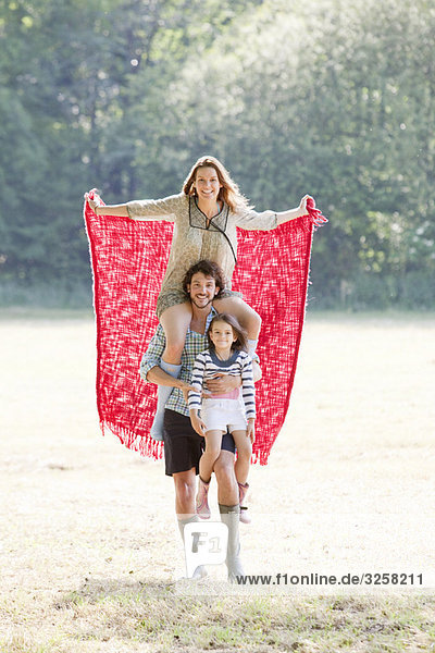 Family with red blanket in country field
