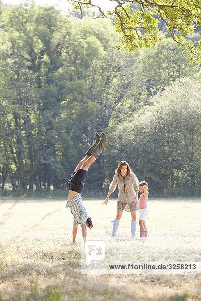 Family playing in country field