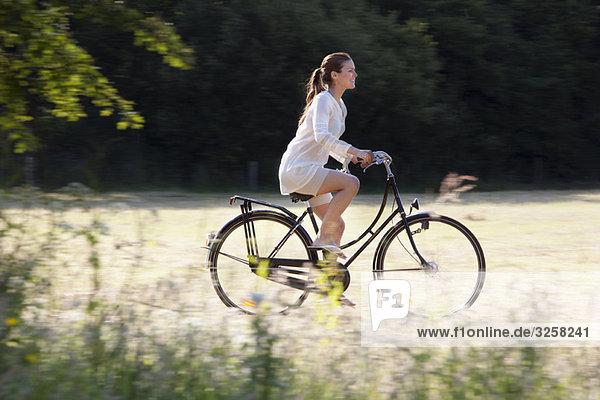 Woman cycling through countryside