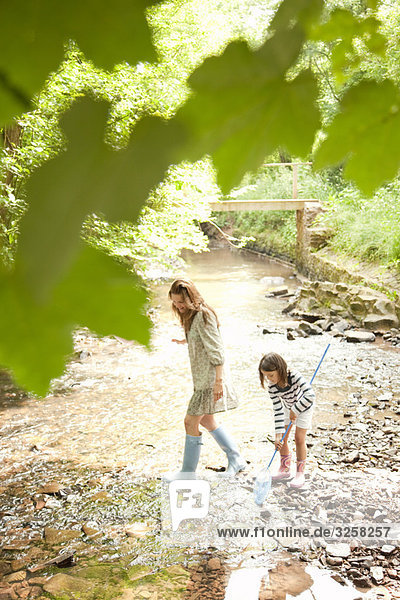 Mother and daughter with nets in stream