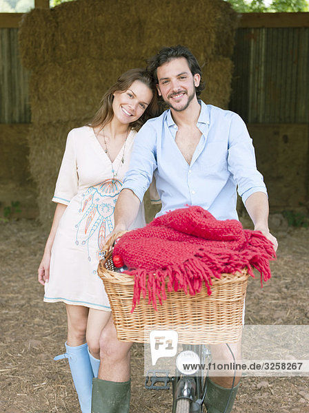 Couple in on bike with picnic basket