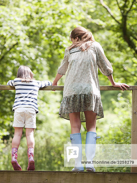 Mother and daughter looking over railing