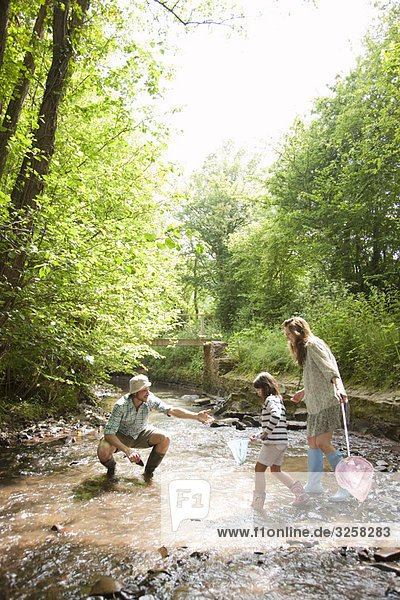 Family playing in country stream