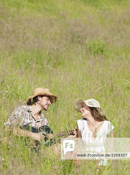 man playing guitar to woman