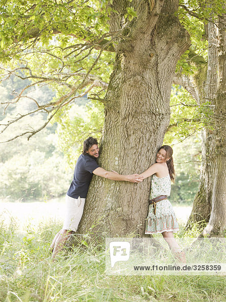 couple with arms around tree