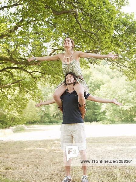 woman on mans shoulders under tree