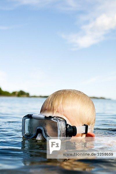 Ein Junge in einem See schwimmen