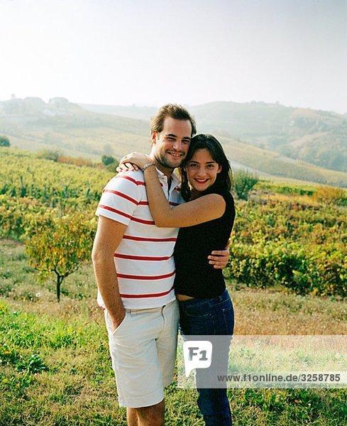 Ein lächelnd Paar in einem Weinberg in Italien.